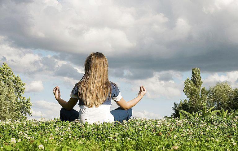 Girl meditating in clover field