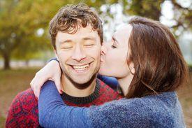 woman kissing man on cheek