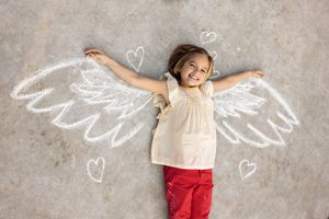 girl laying on ground with chalk angel wings
