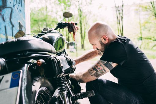 Motorcyclist crouching to repair motorcycle