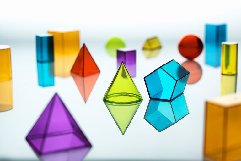 Group of various multi colored geometric shapes resting on a mirror