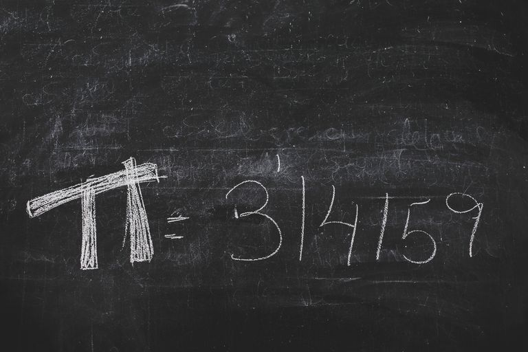 Hand-written Pi numbers on a black chalkboard