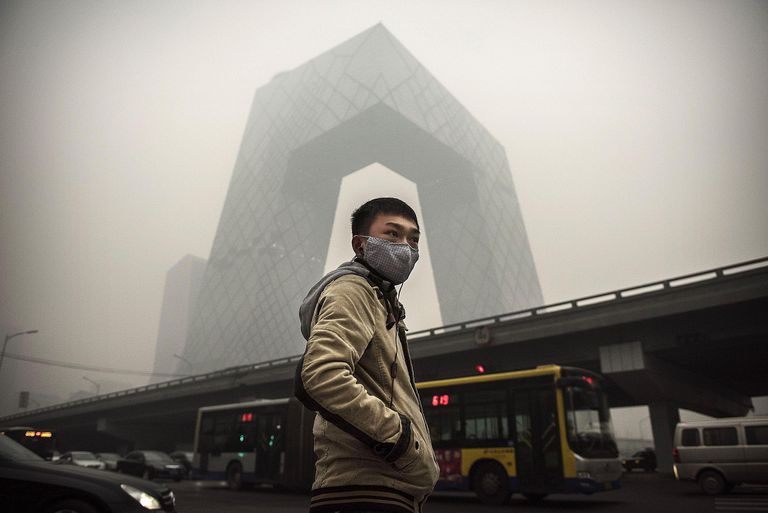 A Chinese man wears a mask to guard against air pollution in Beijing. Much of Eastern and Central China is regularly blanketed by a thick smog caused by coal power plants and industrial production, both of which fuel global warming and climate change, direct results of consumer culture.