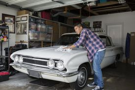 Young man waxing vintage car in garage