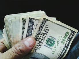 man holding wad of hundred dollar bills