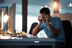 Man sitting at desk holding head