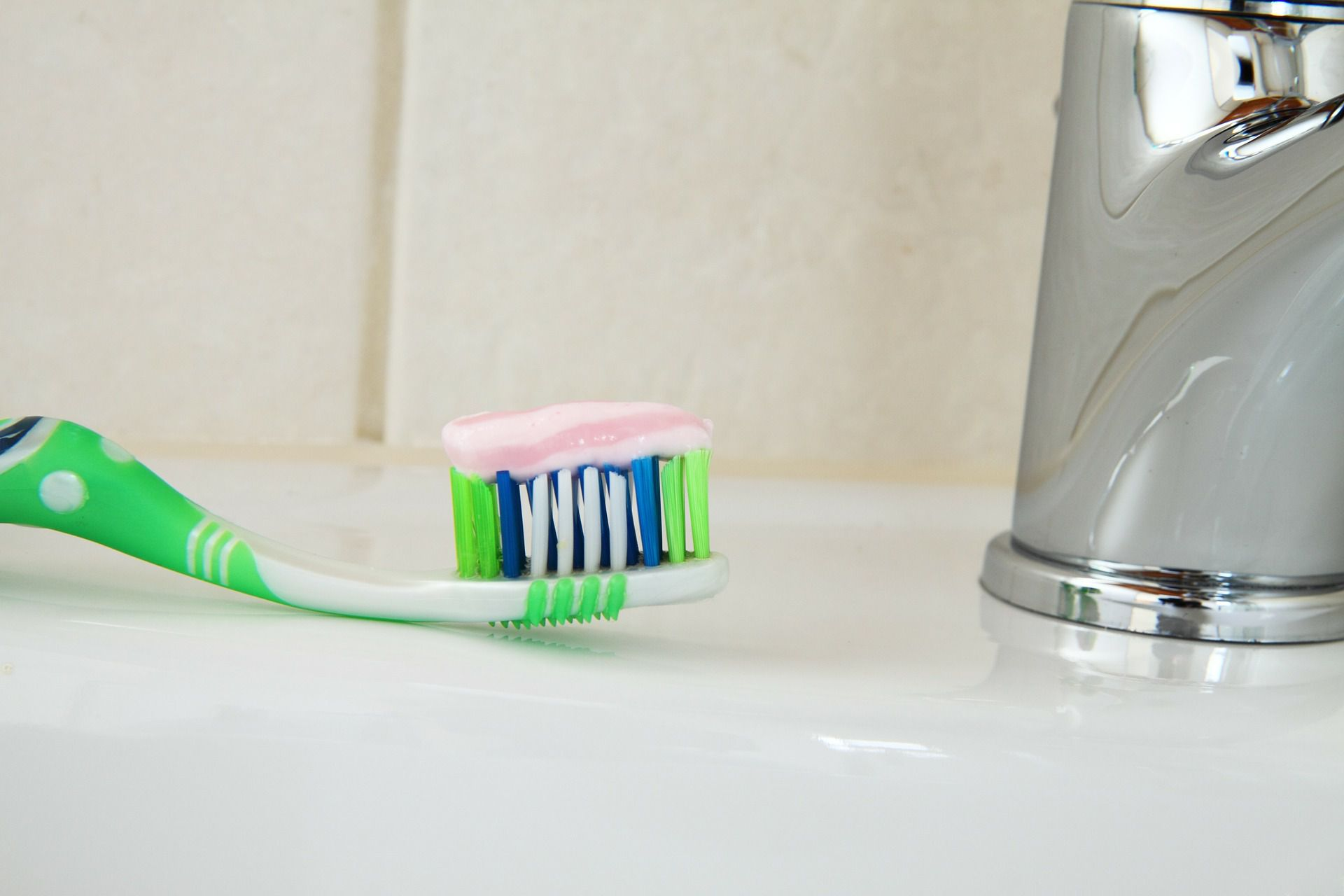 Close up of a toothbrush with toothpaste on it sitting on the sink.