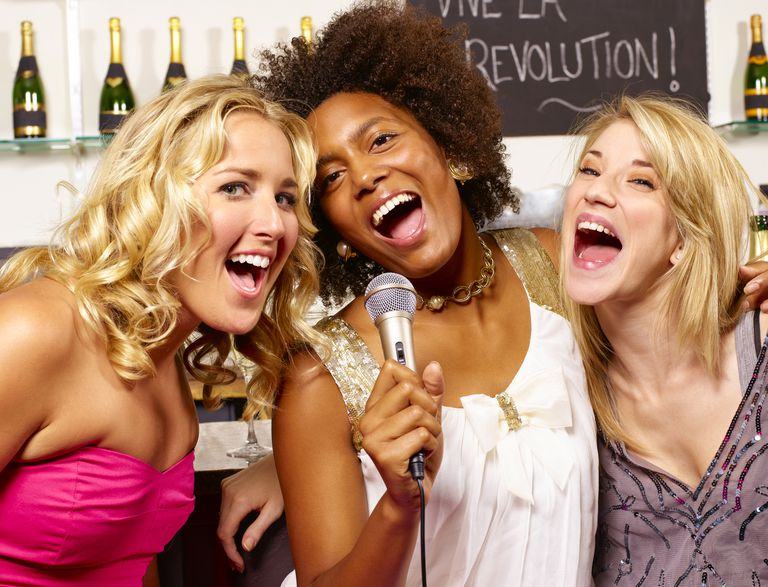 Girls singing together with microphone.