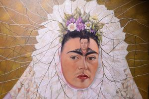 Woman with the face of Diego Rivera painted on her forehead.