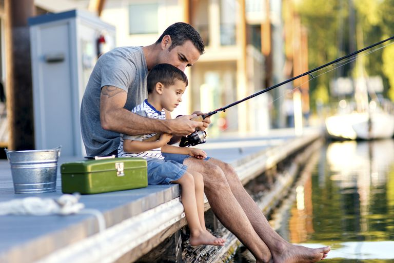 Cute boy gets taught how to fish from dad