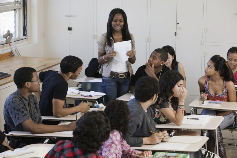 A girl standing up speaking to a class