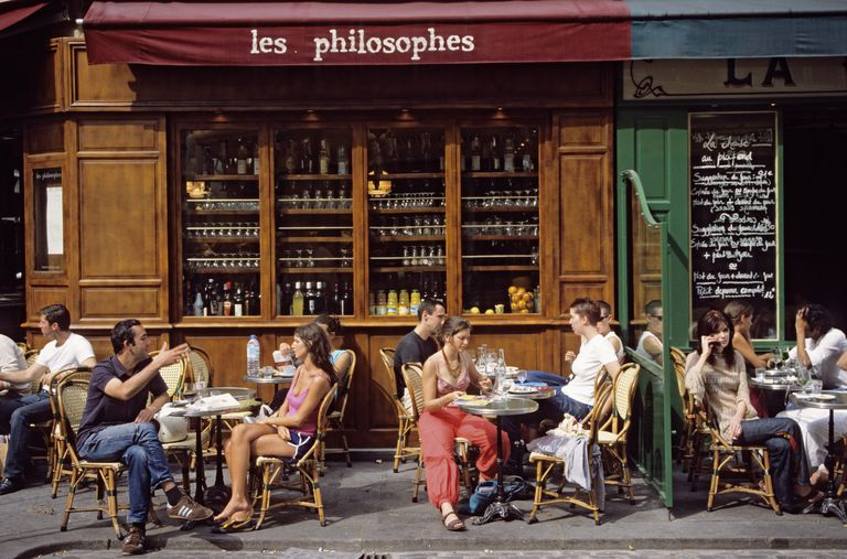 People dine on a cafe terrace in Paris