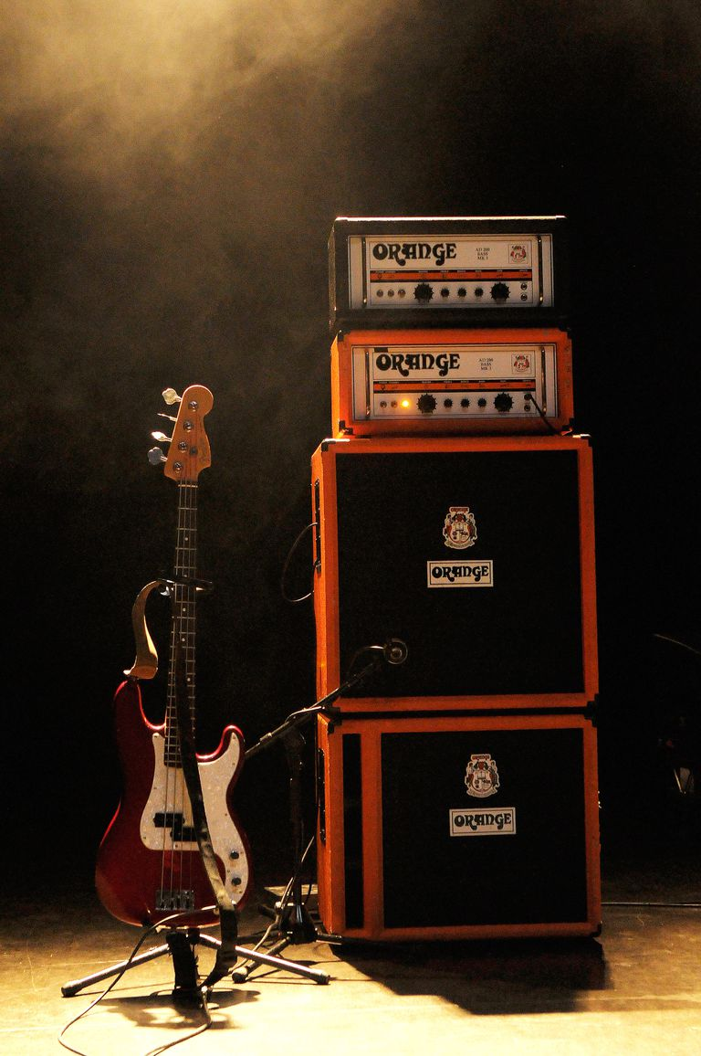 Bass guitar on stand next to stack of amplifiers.