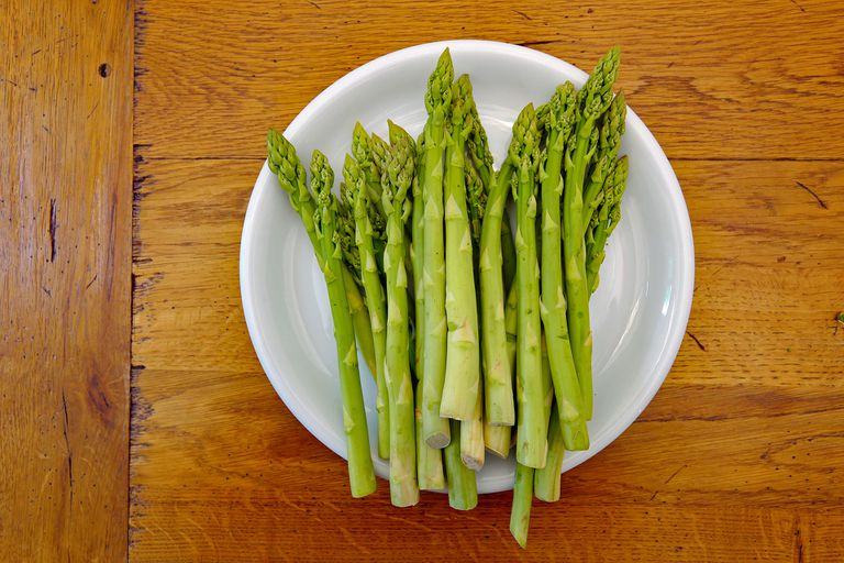 Asparagus spears on a white plate sitting on a wooden table aerial view.