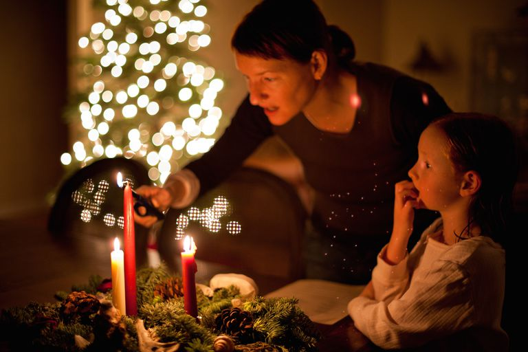 A Mother And Daughter Light An Advent Wreath