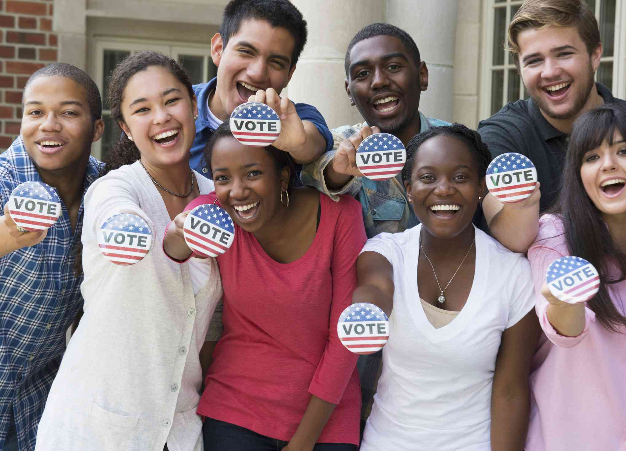 Students holding buttons at voter registration drive.
