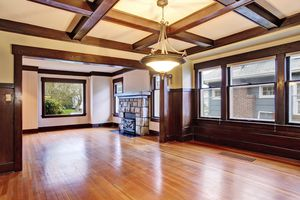 Empty room with wood paneled walls and coffered ceiling. View of family room with old fireplace with stone trim.
