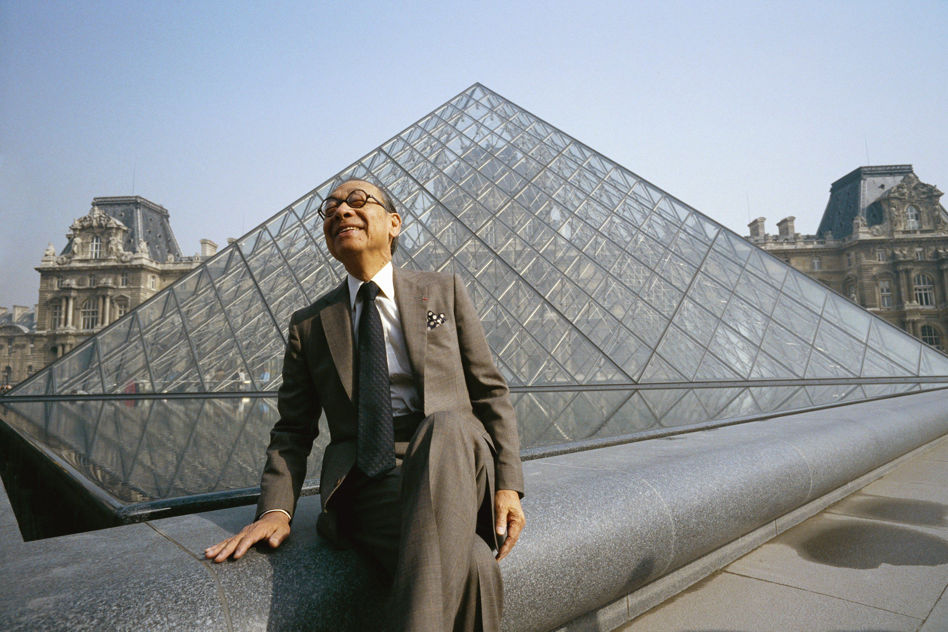 Chinese man in suit sitting in front of a large glass pyramid