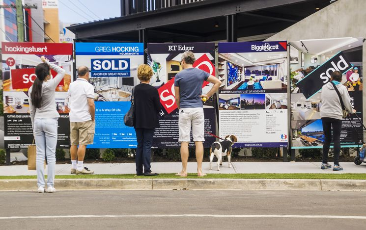 Visitors reading a row of estate agent signs outside a newly-renovated apartment building.