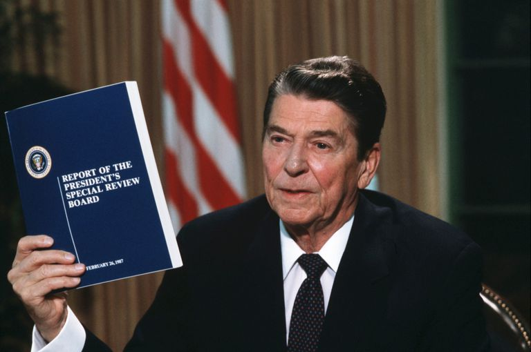 President Ronald Reagan holding a copy of the Tower Commission report on the Iran-Contra scandal