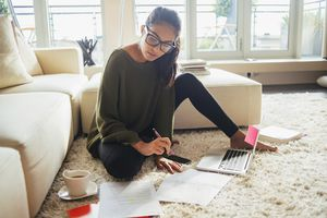 Young woman works on floor with laptop and notes