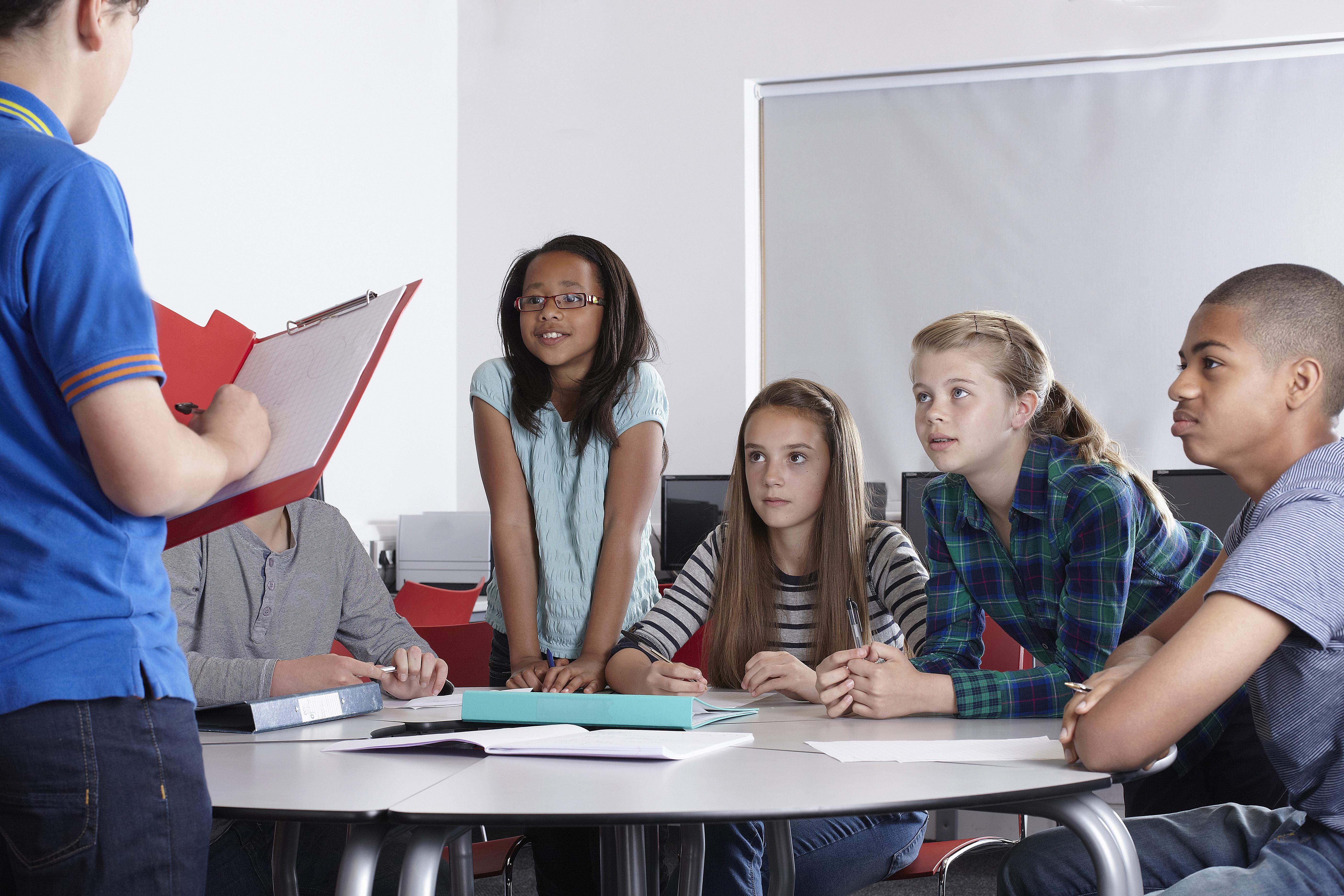 Schüler an einem Tisch, während ein anderer Schüler steht