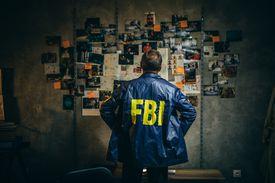 One man, mature FBI agent working on a case in dark office.
