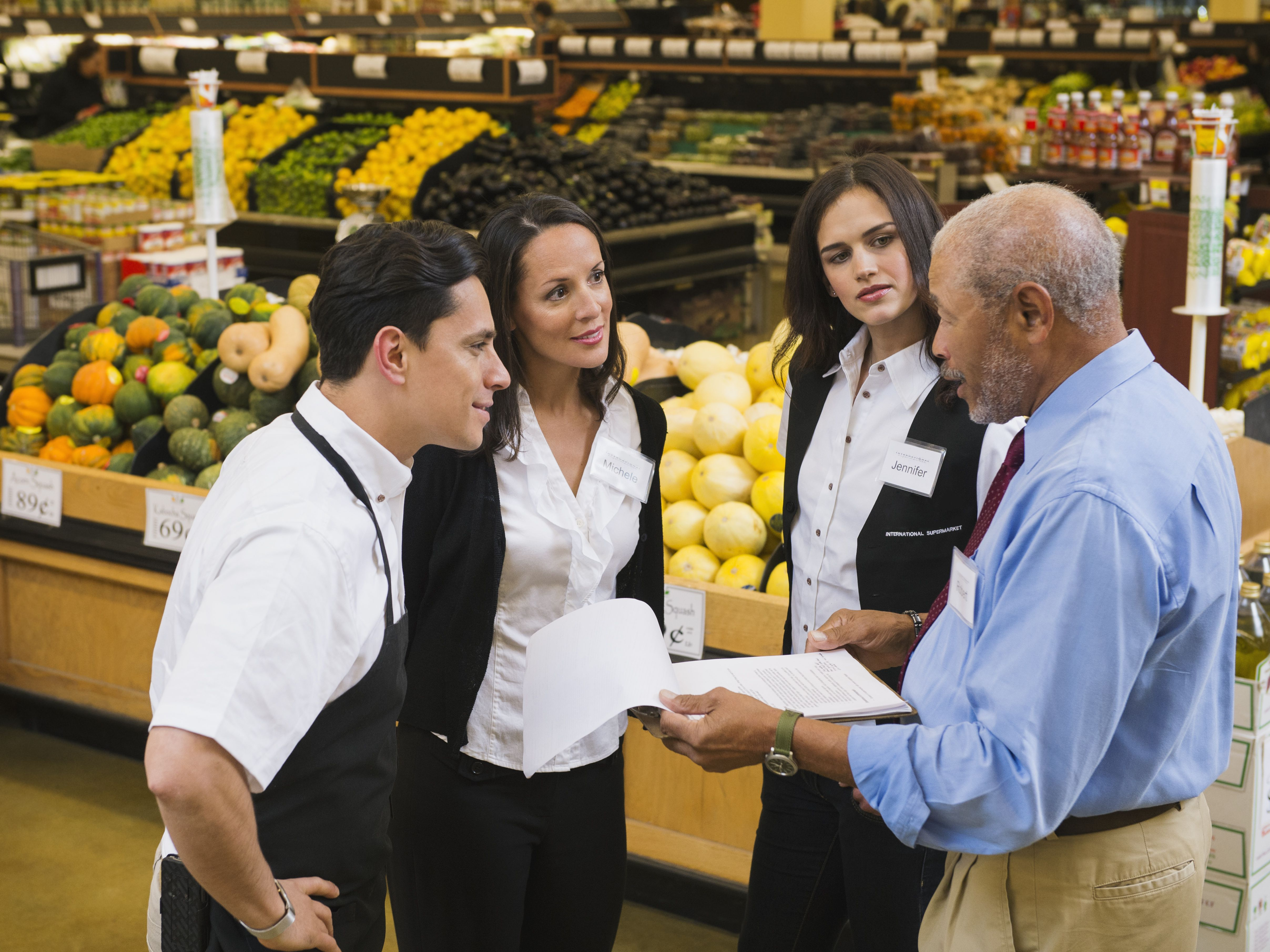 sales manager and workers talking in grocery store