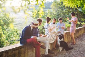 Group of friends relaxing together, sitting on wall, outdoors, eating