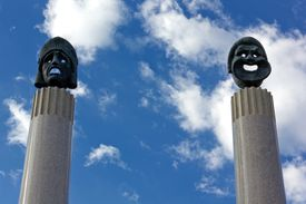 Bronze sculptures of ancient Greek drama masks represent comedy and tragedy atop marble columns