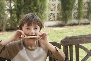 Young boy eating a sardine