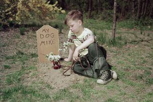 boy at the grave of his dog