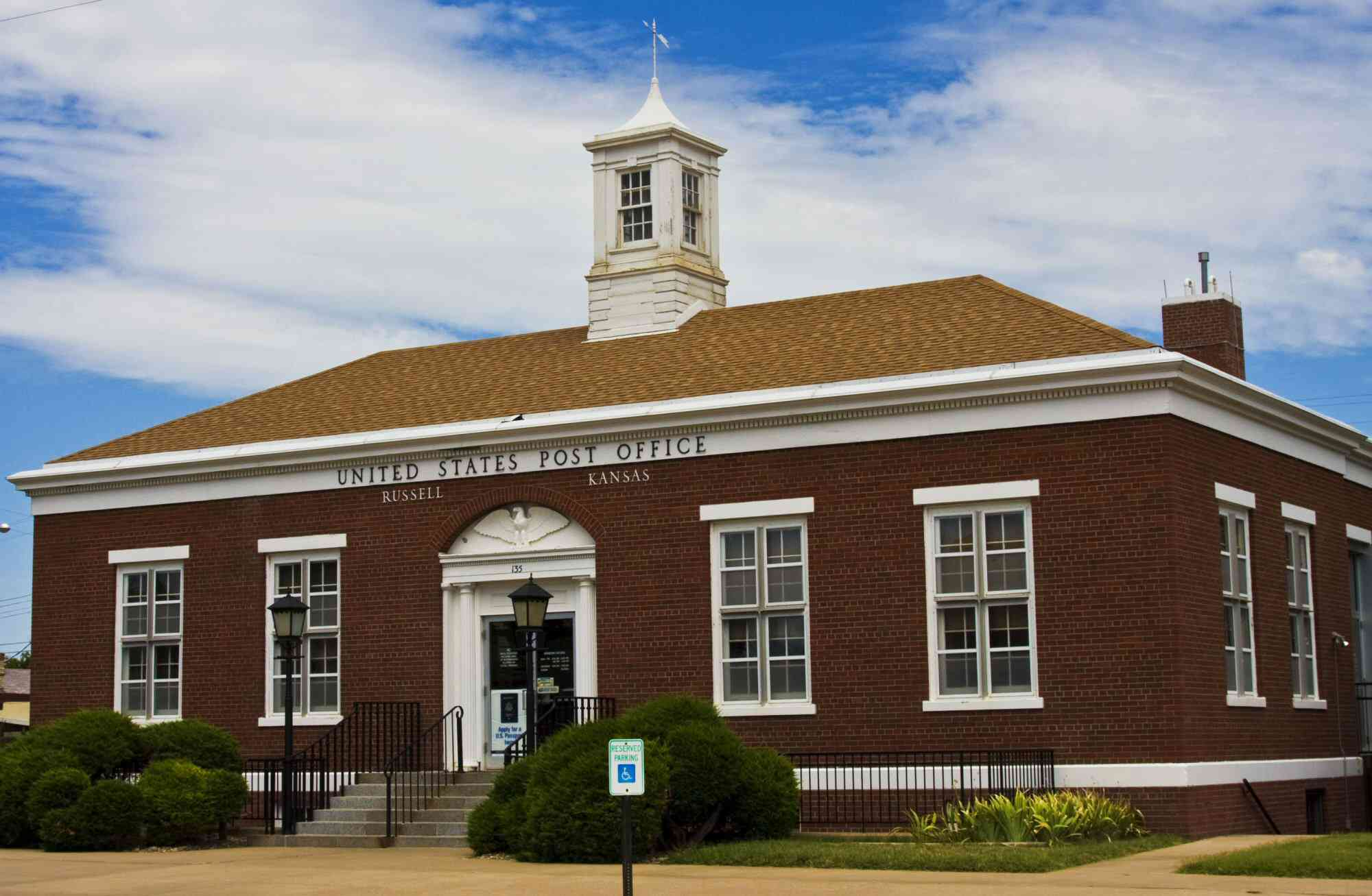Photo of brick post office, 4-over-4 symetrical windows, weathervane, center cupola