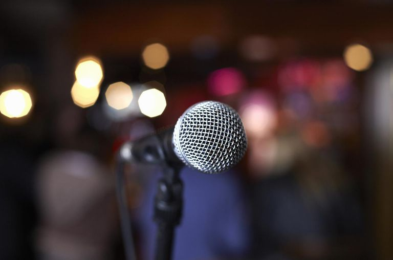 Close up of microphone on stage in lights.