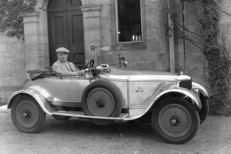 Black and white photo of P.G. Wodehouse behind the wheel of an AC Royal Roadster in front of a residence.