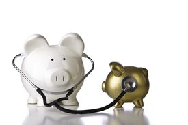 Large piggy bank using stethoscope on smaller, gold one