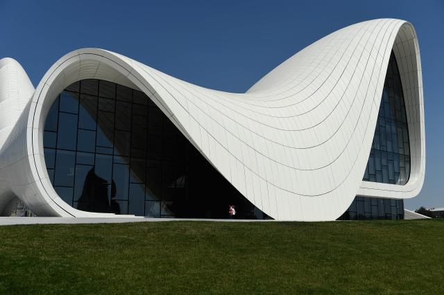 Curving Computer-designed building of glass and solid white fluid folds