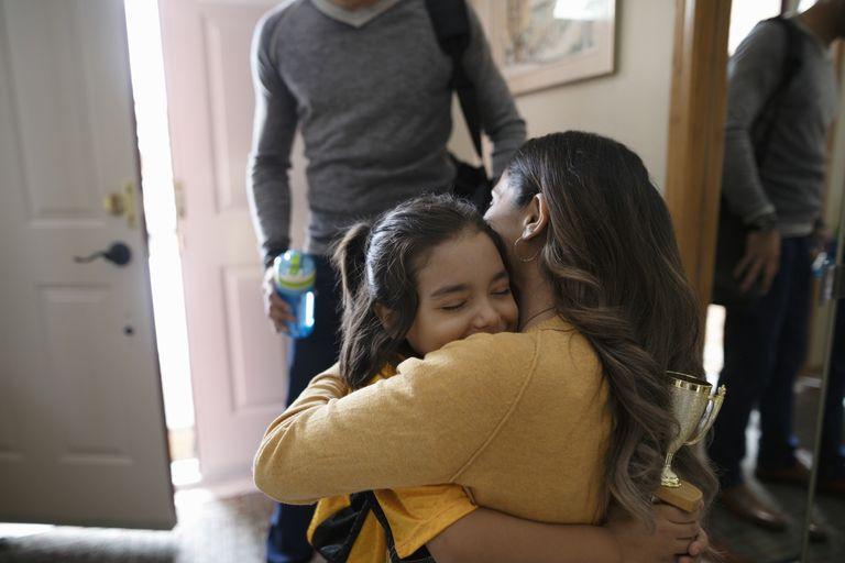 Madre hispana abrazando a hija.