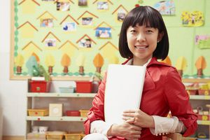 A teacher poses in front of her bulletin boart