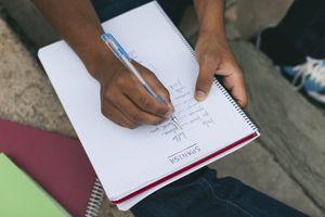 Young man taking notes on Spanish language