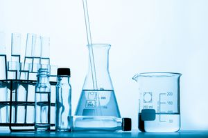 Close-Up Of Conical Flask With Beaker On Table Against White Background
