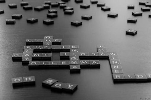"Scrabble tiles spelling out words including ""dilemma"""