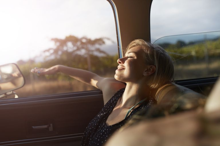 Woman relaxing with arm out of window of car