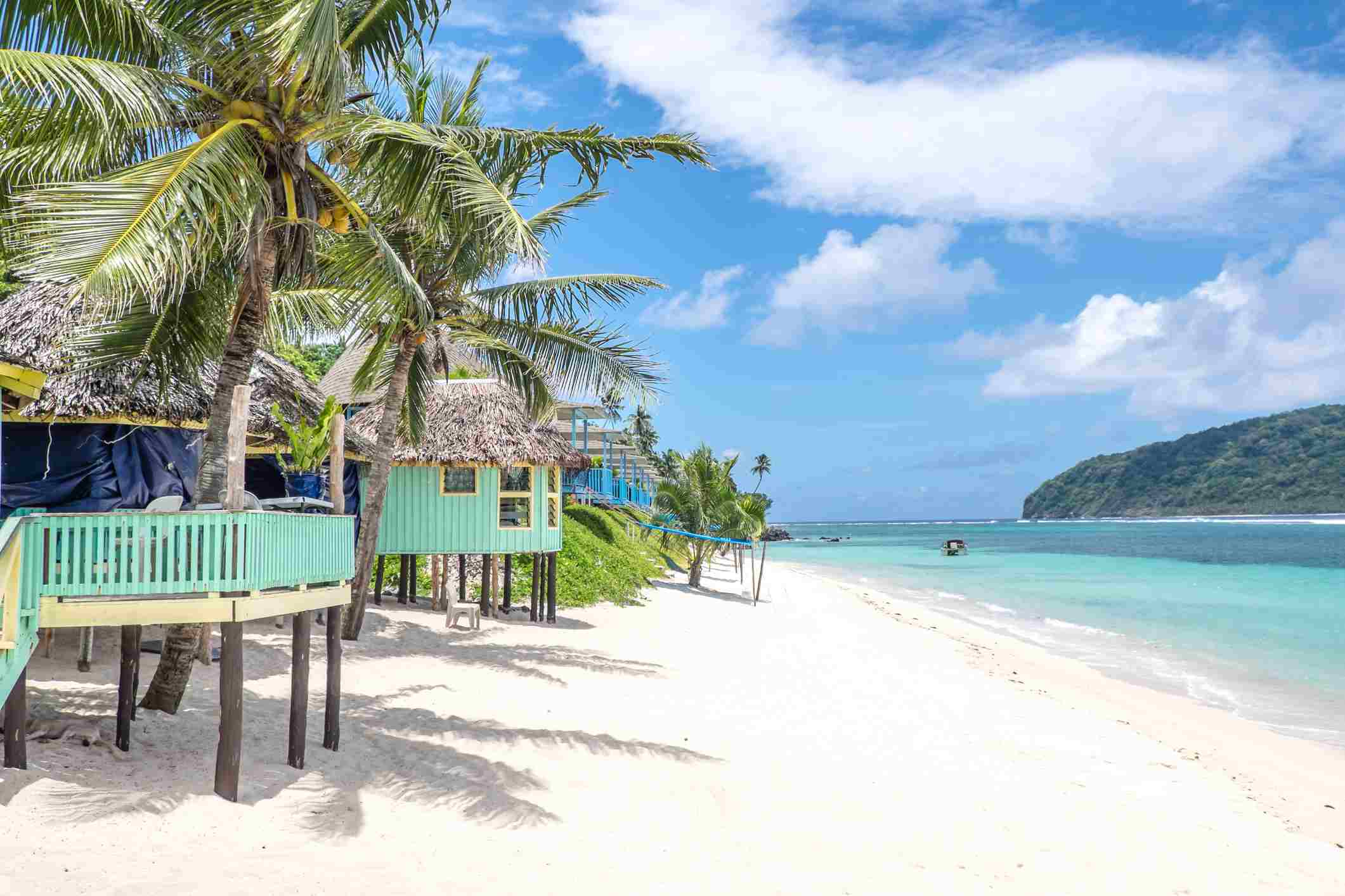 View along Lalomanu Beach, Upolu Island, Samoa, of colorful Samoan beach fale huts that are an alternative to hotel or resort accommodation