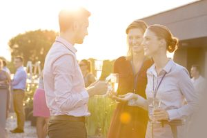 Three people talking at sunset drinking champagne