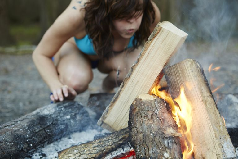 Young woman starting camp fire