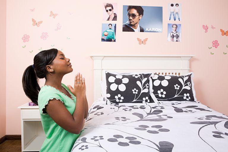 Girl praying in her bedroom