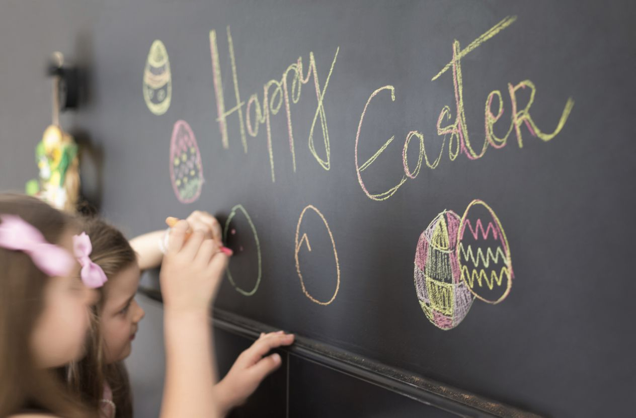 """Two girls writing """"Happy Easter"""" on a chalkboard."""