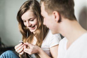 Teenage couple sitting on floor, holding earphones