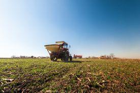 A tractor spreading artificial fertilizers in a field